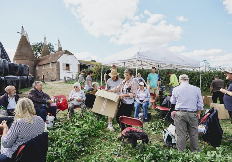 UK hop picking trip - crowd of adults around boxes and chairs in a garden