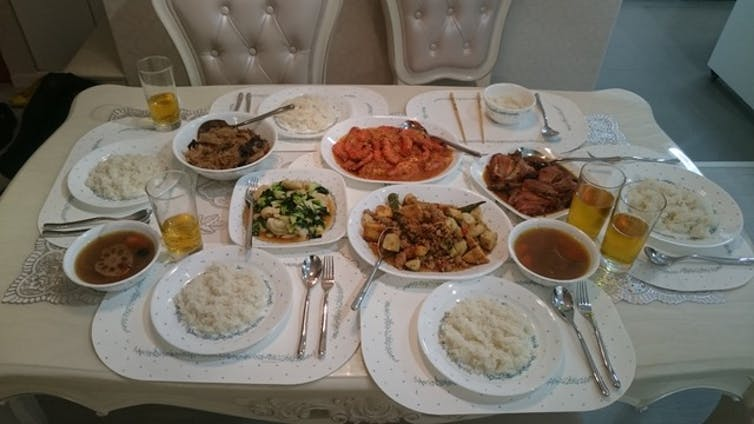 Plates or rice, soup and various food and drinks on a table with chairs