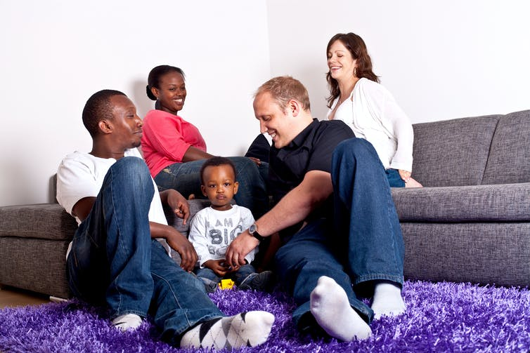 Four adults and a toddler sitting around a living room on couches and the rug, smiling.