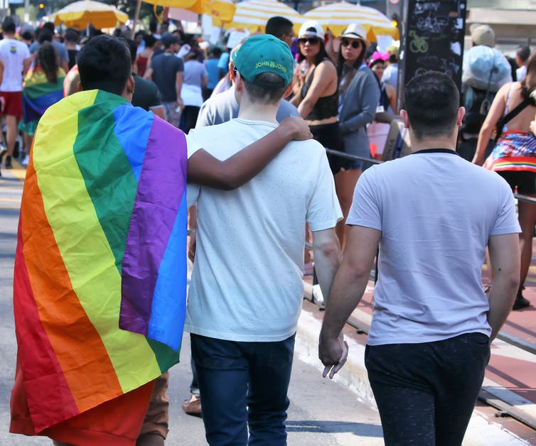 the backs of three people holding hands. One has a rainbow Pride flag draped over their shoulders
