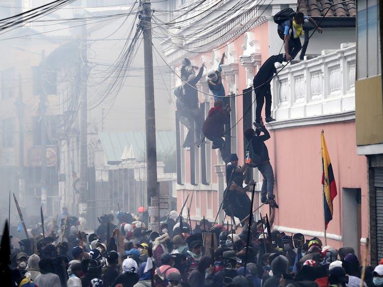 Manifestantes antigubernamentales escalan la fachada de una residencia en busca de una mejor posición para enfrentarse a la policía en Quito (Ecuador), en octubre de 2019.(AP Photo/Dolores Ochoa)