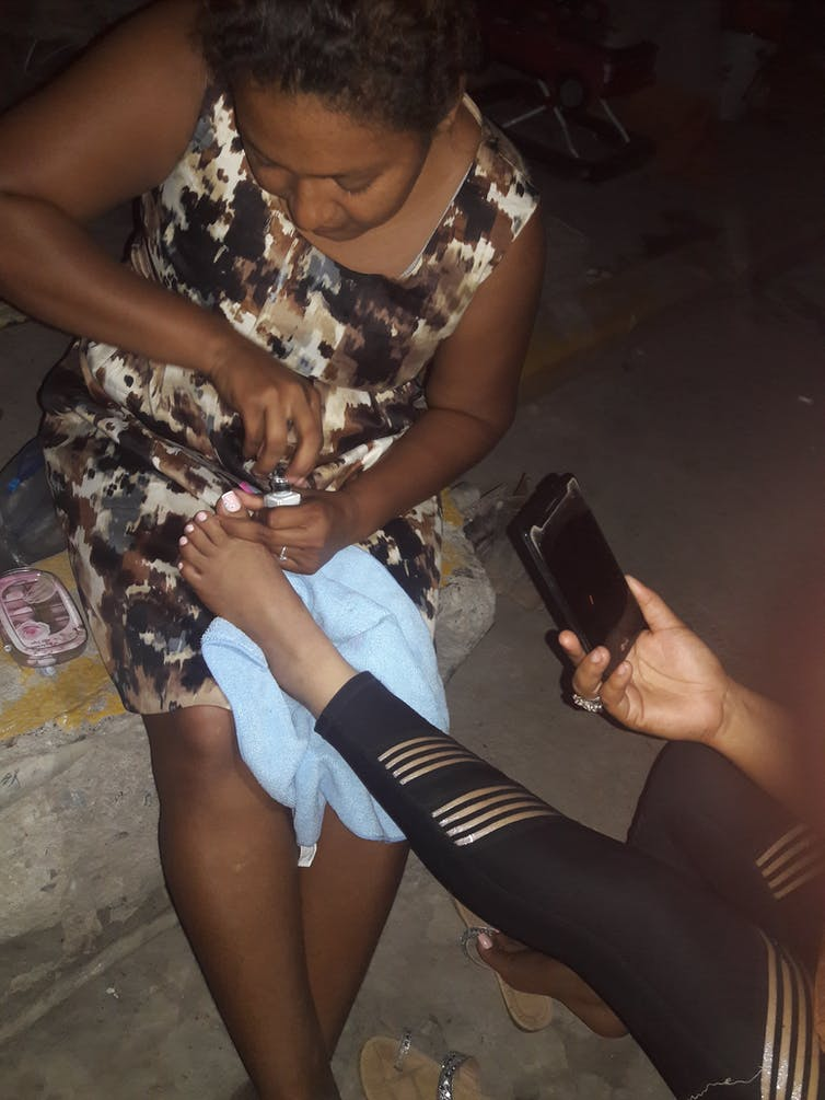 Women exchange pedicures at the improvised refugee camps in Matamoros, along the US-Mexico border. Laura Carrazco, Author provided