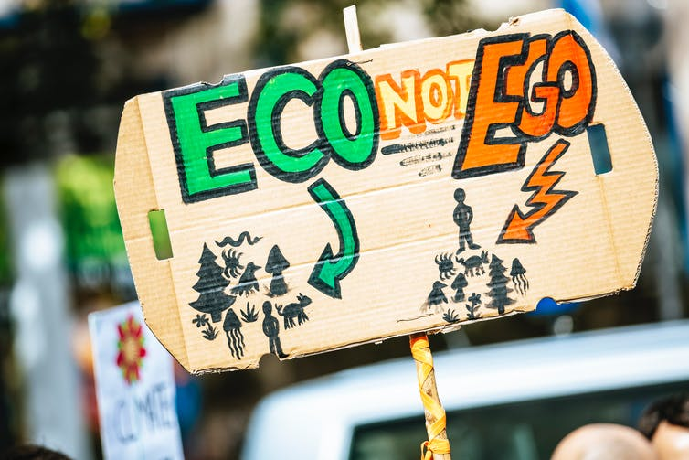 Protest sign at climate protest reading 'Eco not Ego'
