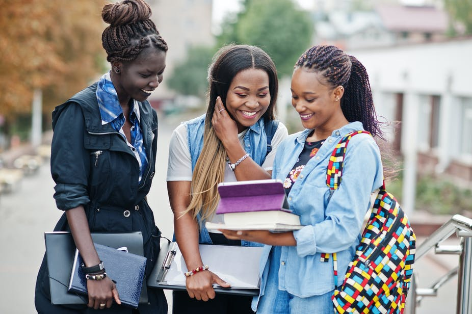 Three young women carrying books and files smile as they look at an iPad together on a stairway.