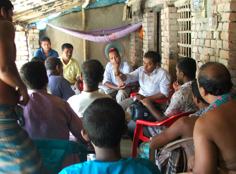 Farmers meet in a group on an outdoor patio