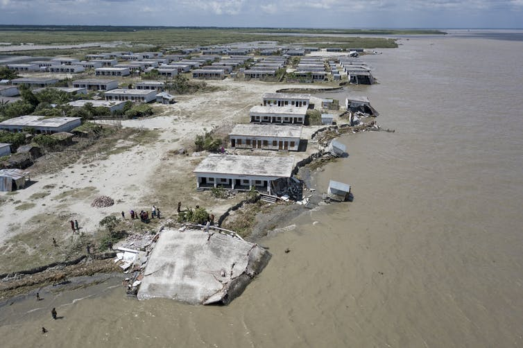 Several houses built along river bank, crumbling and breaking as river erodes the soil