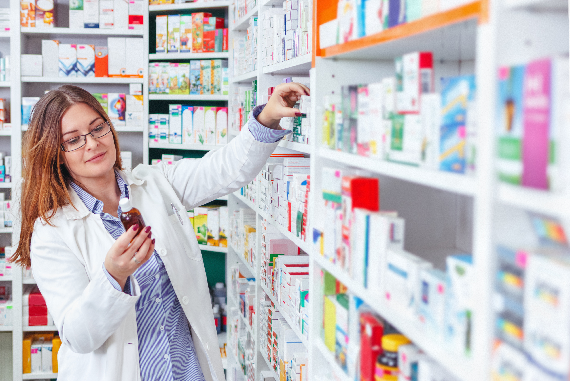 Woman holding a bottle in a pharmacy