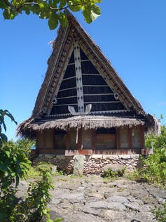 A hut with a large pointed roof, built with local materials.