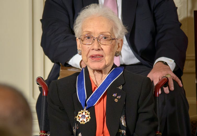 A photograph of Katherine Johnson seated wearing her newly awarded Presidential Medal of Freedom. She is sat in the centre of the photo with a man sat behind her. She wears a black blazer and orange blouse underneath, with small medals pinned into her top lapel. The medal hangs around her neck on a blue ribbon and shows a red and white star in the middle of a gold frame. In the very centre of the medal, there are white stars on a navy back ground. Katherine Johnson looks head on at the camera from behind her glasses and is poised semi-formally.