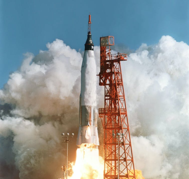 A rocket in the centre of the image takes off next to vertical red scaffold. Dark grey smoke engulfs the image from the left-hand corner to the top, becoming a white colour on the right-hand side. Bright white-yellow fire is showing from underneath the rocket as it lifts.