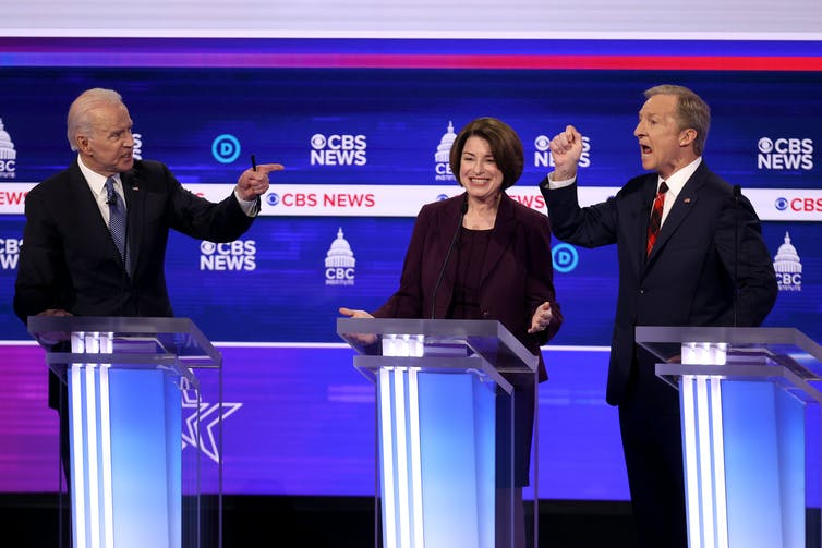 Democratic presidential candidates former Vice President Joe Biden (L) and Tom Steyer (R) debate as Sen. Amy Klobuchar (D-Minn.) reacts during the Democratic presidential primary debate, Feb. 25, 2020 in Charleston, South Carolina. Getty/Win McNamee