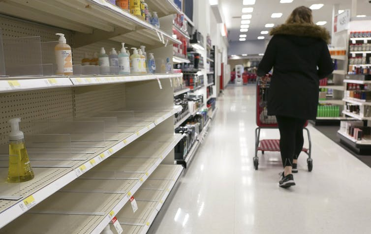 Woman walking through bare store aisle