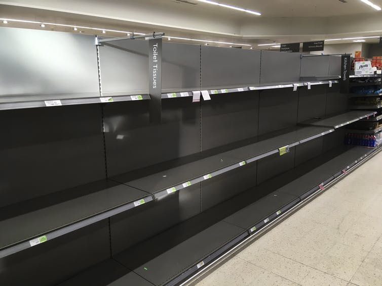 Shelves stand empty in the aisle for toilet paper at the Waitrose supermarket in Surbiton, south west London, on March 11, 2020