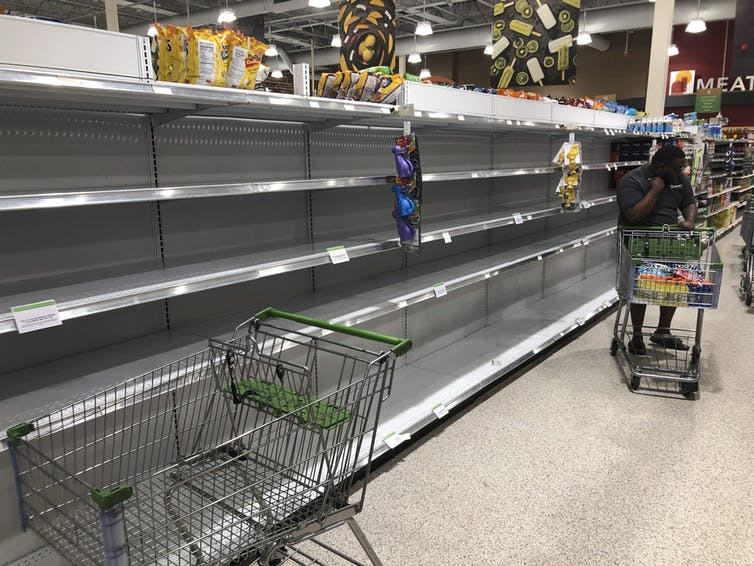Empty shelves where water is sold at a grocery store are shown in August 2019, in North Miami, Fla. as Hurricane Dorian approached