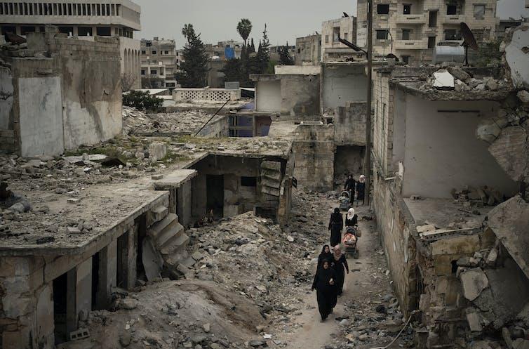 Women walk among airstrike-ruined buildings in Idlib, Syria.AP Photo/Felipe Dana