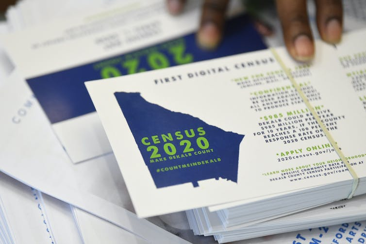 A worker gets ready to pass out instructions in how fill out the 2020 census during a town hall meeting in Lithonia, Georgia. AP Photo/John Amis