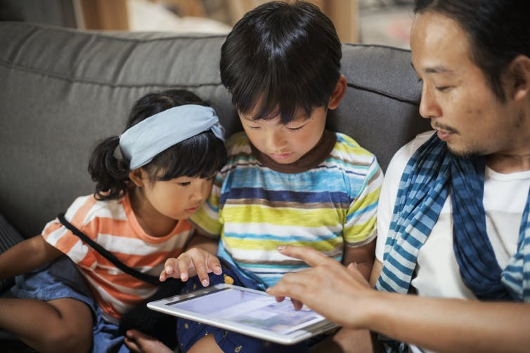 father and children on tablet to enhance family health