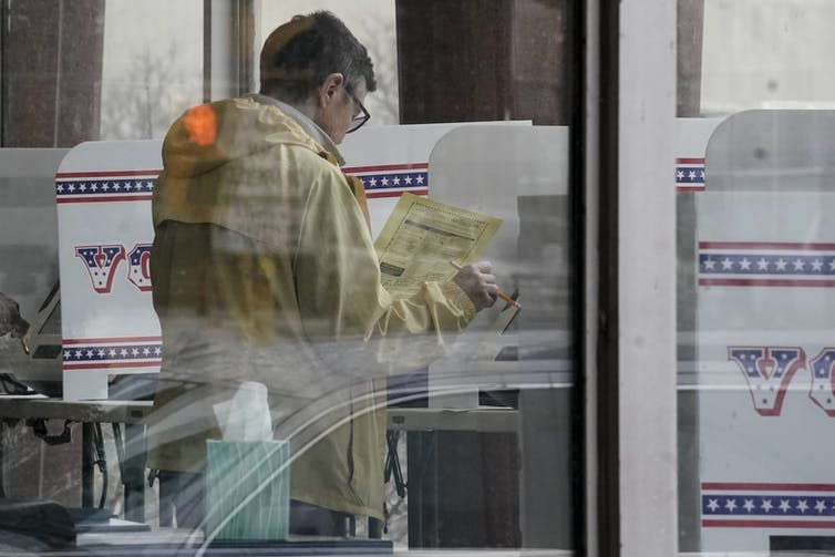 A Wisconsin voter casts a ballot ahead of primary election day, avoiding lines and finding a more convenient time to vote. AP Photo/Morry Gash
