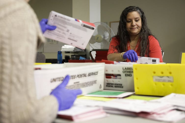 Election workers sort mailed-in ballots in Washington state on March 10. Jason Redmond/AFP via Getty Images