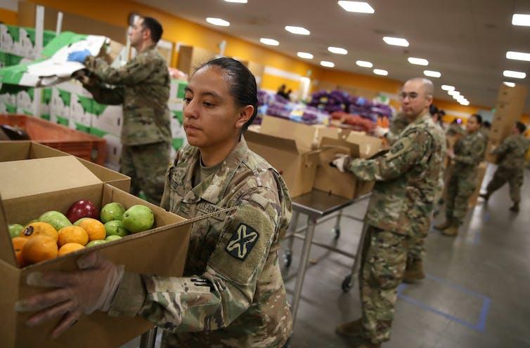 California National Guard members help distribute food at food banks that have seen volunteer numbers plummet amid the coronavirus outbreak.Justin Sullivan/Getty Images