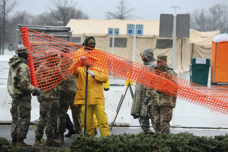 Members of the Maryland National Guard put up fencing around an area slated to become a screening site for potential coronavirus patients. Chip Somodevilla/Getty Images