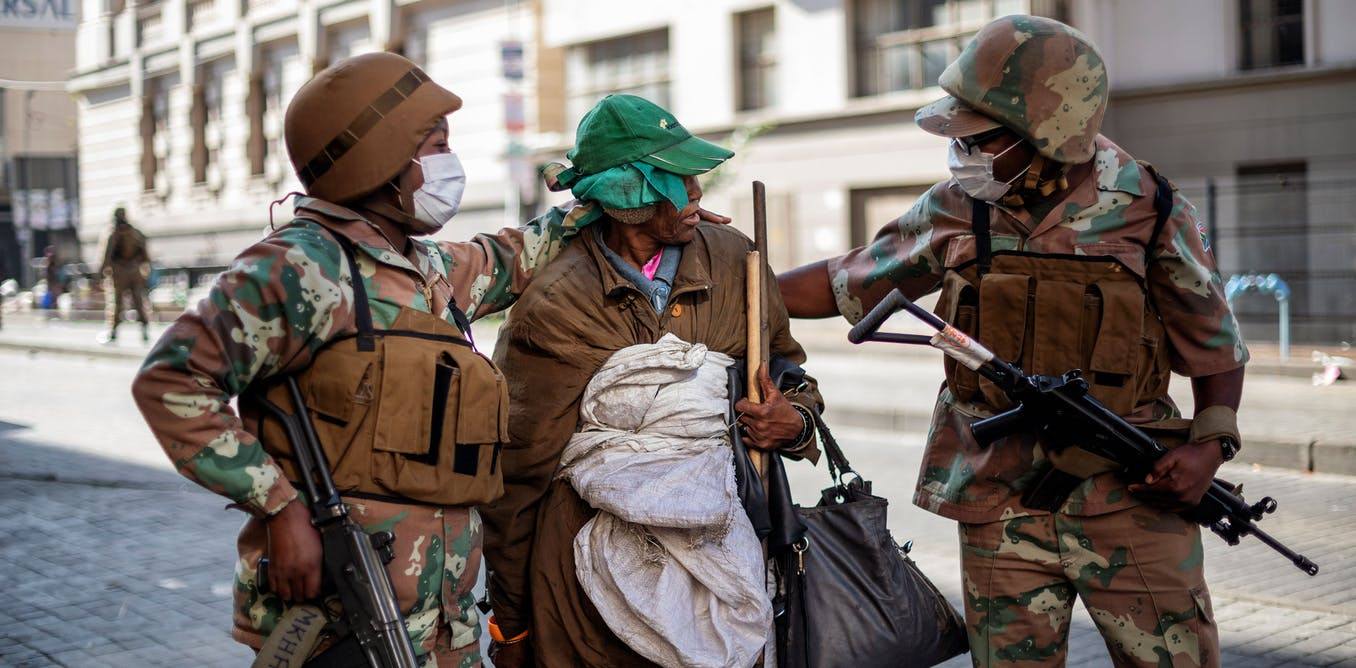 Soldiers escort a homeless woman to a gathering point in the Johannesburg CBD during the nationwide Covid-19 lockdown. Michele Spatari/AFP-GettyImages