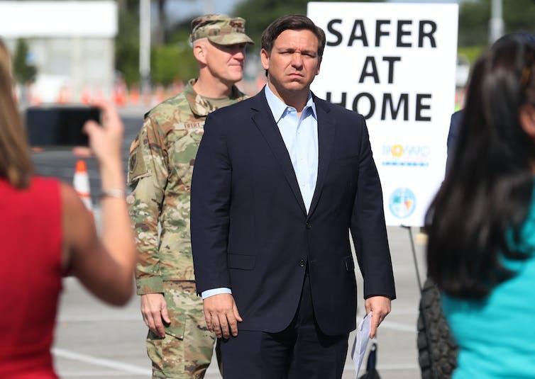 Gov. Ron DeSantis standing in front of Safer at Home sign