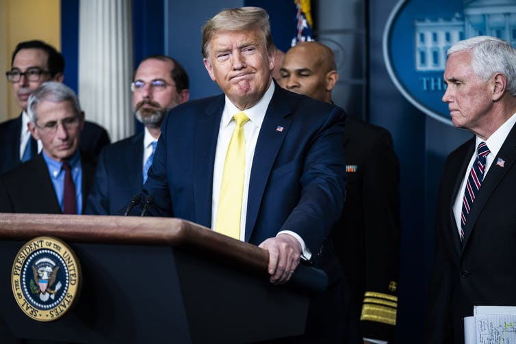 President Trump at press briefing with members of his cabinet standing in the background