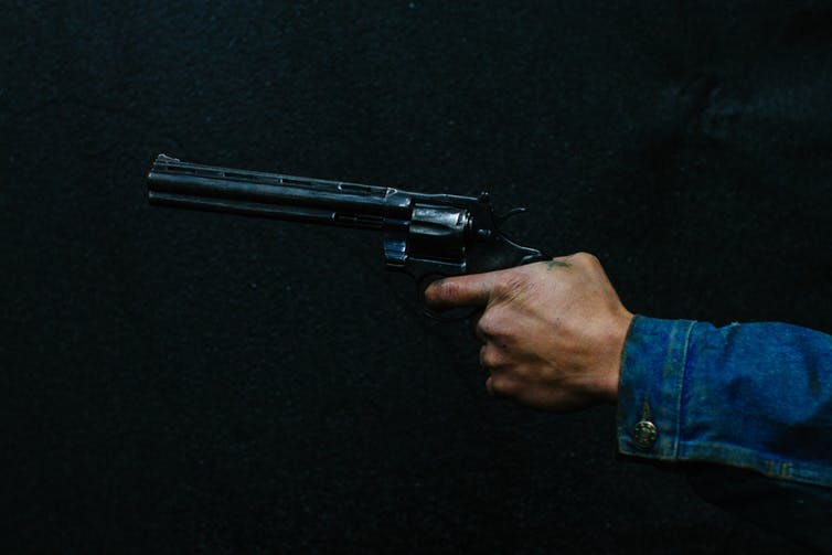 A hand holding a gun with the finger on the trigger.