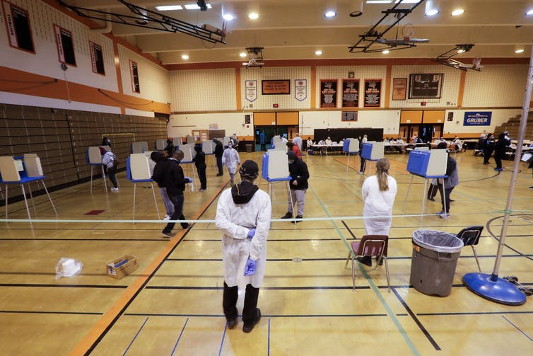A Milwaukee high school gym was converted into a polling place on April 7, with voting booths set apart from each other and election workers wearing masks and gloves. AP Photo/Morry Gash