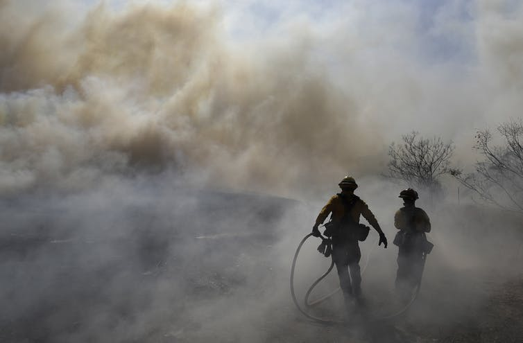 firefighters standing on smoky field