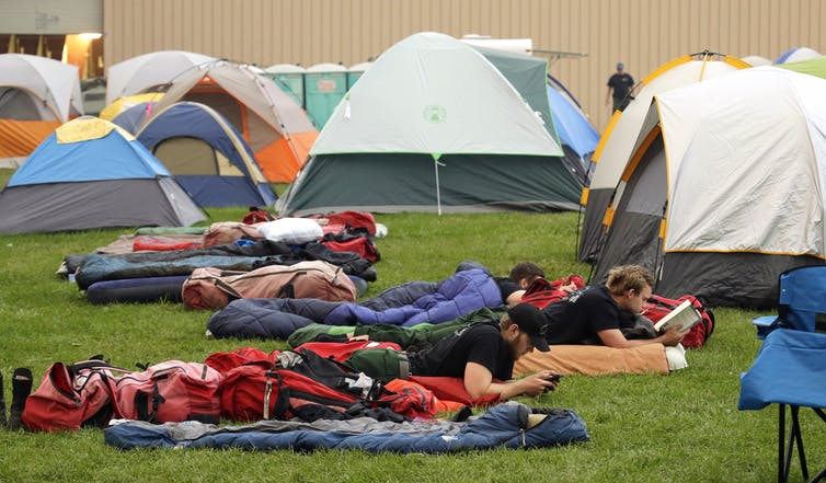 tents and sleeping bags set up on a lawn, firefighters rest on sleeping bags, photo