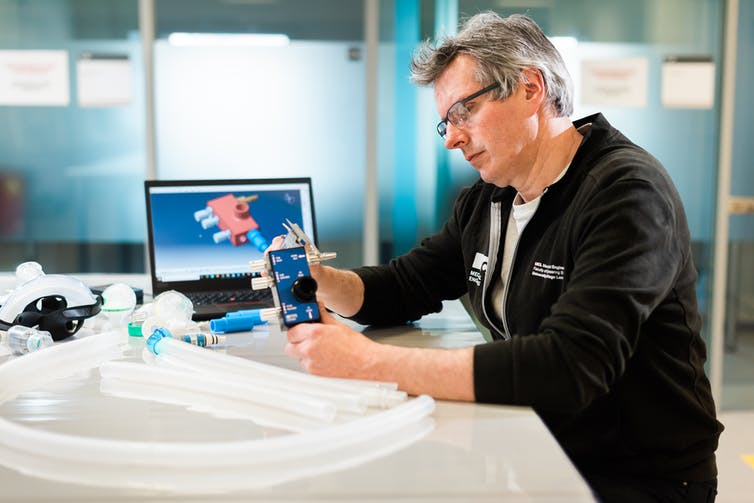 Prof Tim Baker examines the finished device. James Tye / UCL