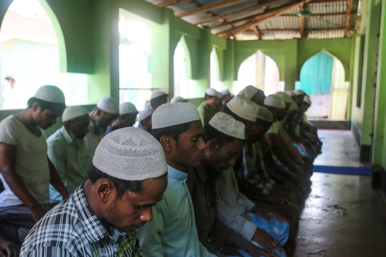 men bowing at prayer in mosque, photo by Getting images, open link to view all details