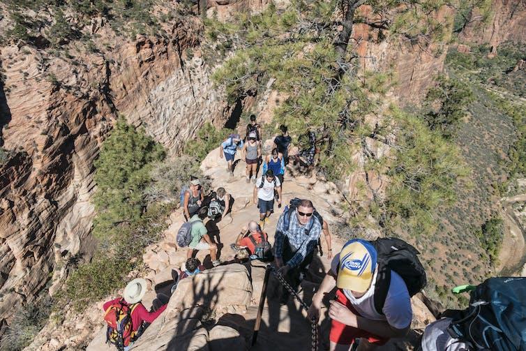 Tourists hiking up mountain, photo