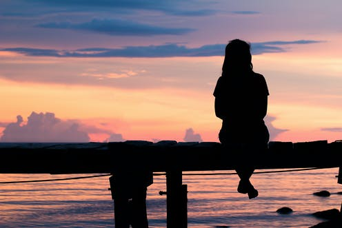 Image of a woman sitting alone on a bench in sunset.