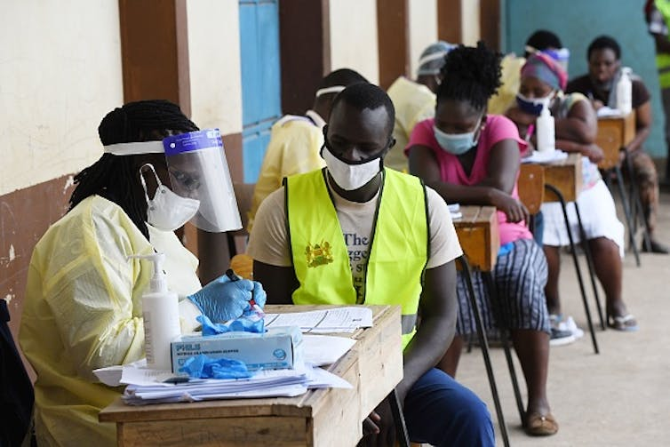 Health care workers testing people in Nairobi, Kenya during a mass testing exercise for COVID-19. Photo by SIMON MAINA/AFP via Getty Images