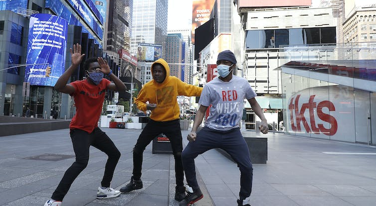 Three boys dancing in Times Square, New York City.