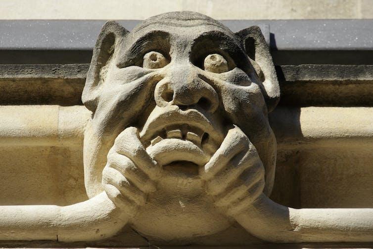 Una extraña gárgola, mitad hombre y mitad cerdo, masca algo en una fachada del Exeter College, en la Universidad de Oxford.Apexphotos / Getty Images
