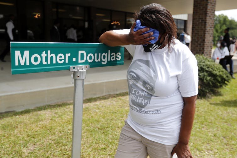 A black woman wearing a George Floyd T-shirt rests her forehead in her hand (or wipes at her face). You can't see her face, but her stance is tired.