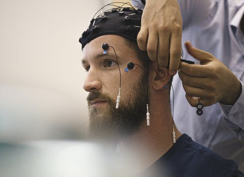 A technician's hands attach electrodes to a man being prepared for cognitive assessment with an electrode cap and electrodes on his face.