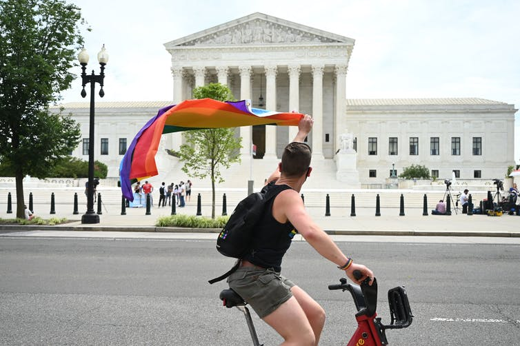 A man waves a rainbow flag as he rides by the Supreme Court on June 15, 2020. JIM WATSON/AFP via Getty Images