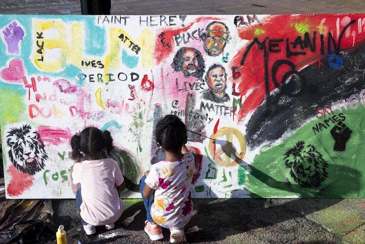 Two children paint a mural at Black Lives Plaza, Washington D.C. AAP/EPA/Michael Reynolds