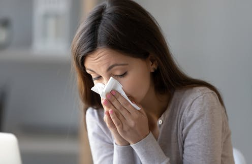 Woman blowing her nose with a tissue