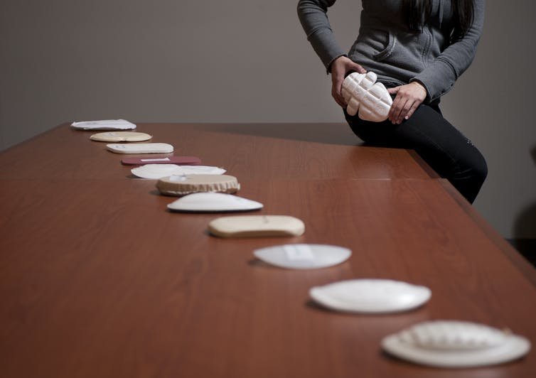 A woman sits on the corner of a table demonstrating the fit of a hip protector pad. Several types of hip pads are arranged on the table
