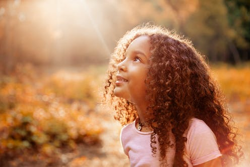 A young girl looking up to the sun.