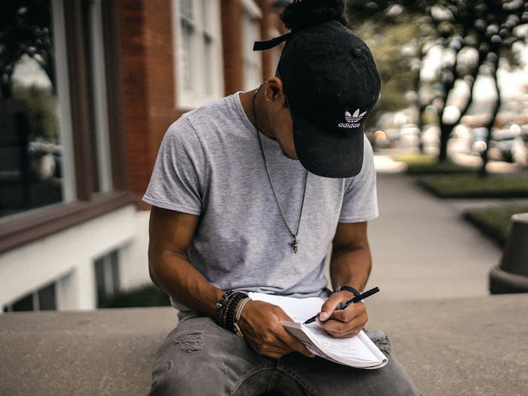 A young Black man writes in a notebook.