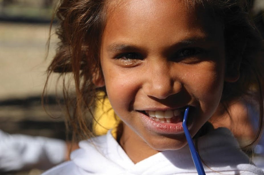 Girl smiling and showing teeth with toothbrush in her mouth.
