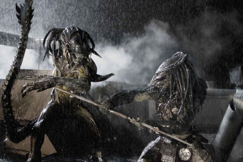 A scene from the move Alien vs. Predator shows two dreadlocked aliens fighting with spears in a rainstorm.