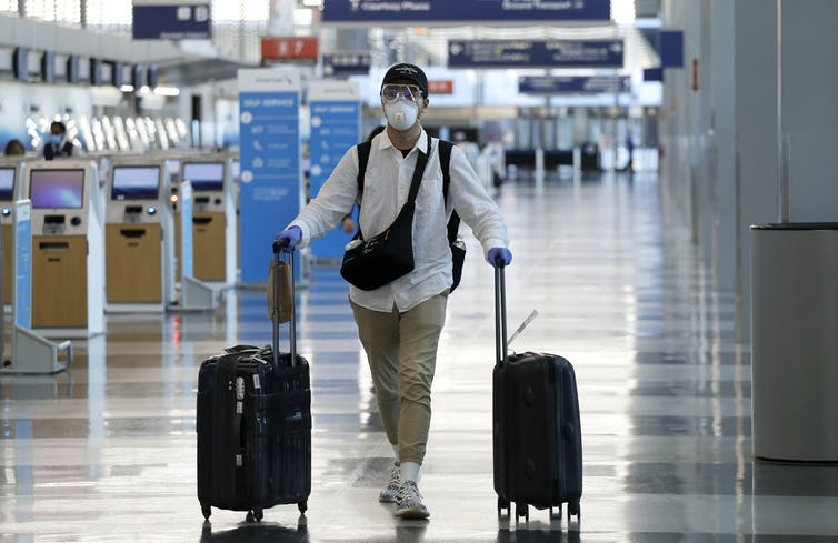 Passenger in an airport wears a mask and gloves